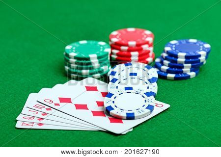 Casino green table with chips and royal flush of playing cards. Poker game concept