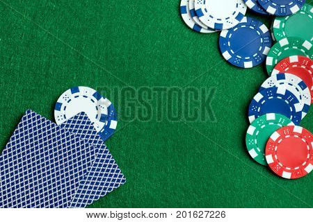 Casino green table with chips and play cards. Poker game concept