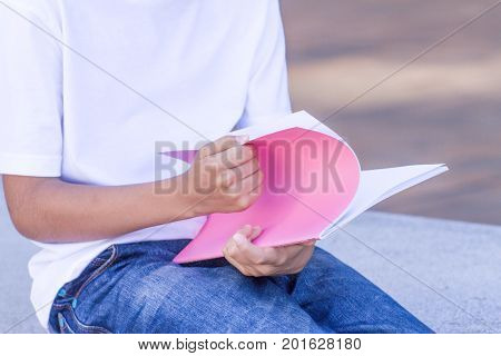 Kid's hand and books. Boy sitting and leaning on closed books