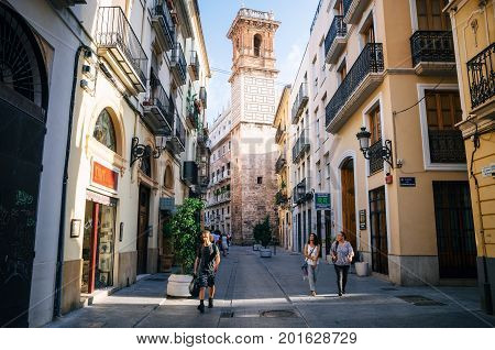 Valencia Spain - June 2 2017: Tourists walk along the street of the old town in the center of Valencia in front of the Bell Tower of Saint Bartholomew. Spain.