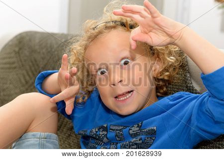 a little boy with blond and curly hair making faces