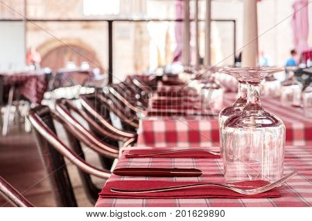 The tables of a street cafe, ready for dinner, with glasses for wine and forks and knives on red chequered tablecloths, and rows of chairs, selective focus, with a place for text