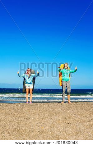 Two happy smiling girls with boogie boards standing on windy beach showing thumb up - ok sign. Blue sky background. Tenerife Canary islands Spain. Vertical multicolored summertime outdoors image.