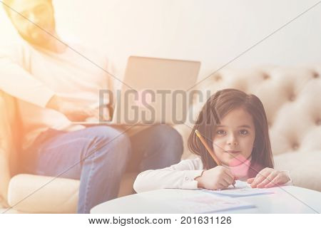 Talented kid. Incredible gifted creative girl drawing nice pictures with a pencil while her dad sitting behind her and adoring his child