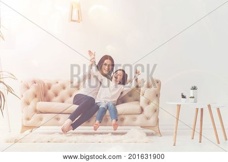 Great moments. Two lively nice young ladies spending time together while sitting on pink couch and goofing around