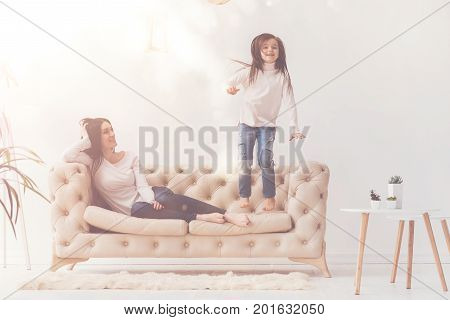 Cute rascal. Enthusiastic charming active child having fun in living room and jumping on pink couch while the mom adoring her kid