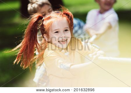 adorable happy red haired girl playing tug of war with friends in park