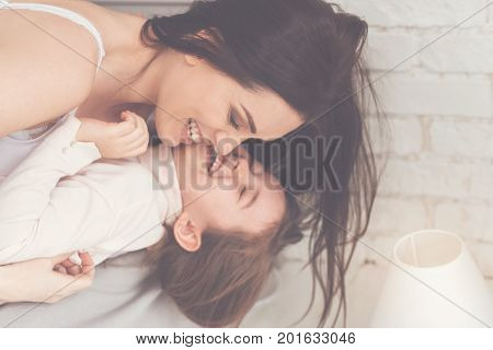 Strong emotions. Tireless sincere hilarious daughter and mom sharing a lovely emotional moment while hugging and goofing around in bed in the morning