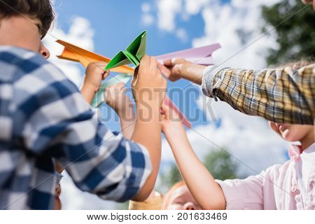 cropped shot of little kids holding colorful paper planes