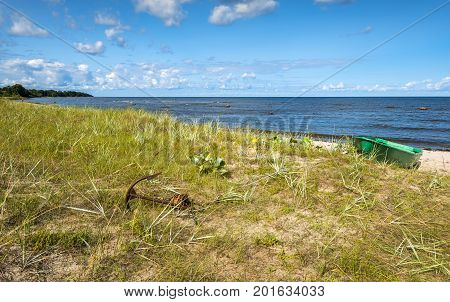Coastal landscape with anchored fishing boat at sandy beach, Baltic Sea