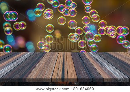 Empty wooden table or plank with bokeh of rainbow soap bubbles from the bubble blower on background for product display.