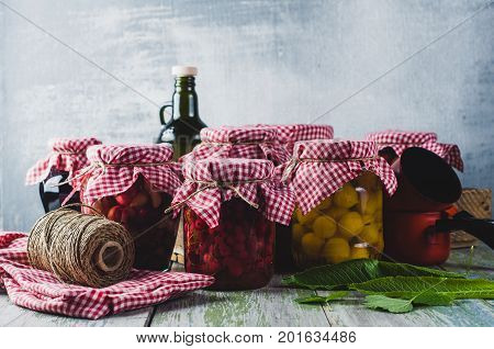 Homemade Canned Vegetables And Fruits In Glass Jars On A Wooden Table