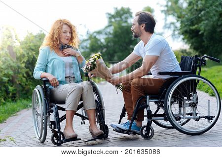 What a surprise. Pleasatn senior wheelchaired woman getting flowers from her husband and sitting in the wheelchairs while resting in the park on the weekend