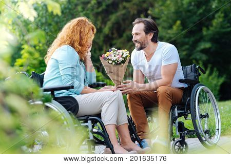 In love with you. Pleasant smiling senior man presenting a bunch of flowers to his nice wife while sitting in the wheelchairs while spending time together in the park