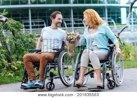 Upbeat mood. Cheerful senior man presenting a bunch of flowers to his beautiful loving wife while sitting in the wheelchairs and enjoying the walk outdoors