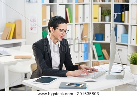 Smiling middle-aged white collar worker writing response email to business partner while sitting at desk, interior of modern open plan office on background
