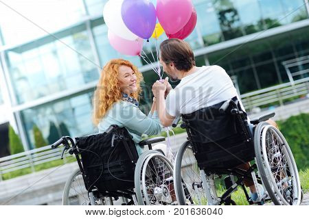 Catch the moment. Positive senior wheelchaired couple sitting in the wheelchairs and holding balloons while looking at each other