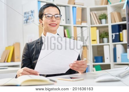 Smiling white collar worker in eyeglasses doing paperwork while sitting at desk, interior of modern open plan office on background