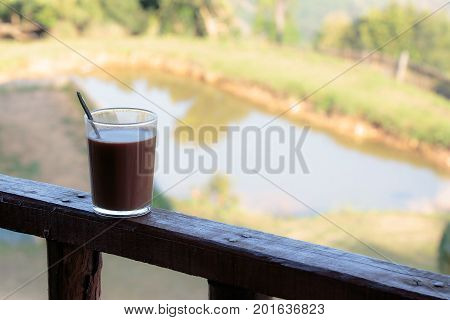 Hot chocolate in glass on the wooden balcony of house or resort home.
