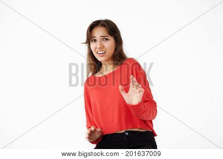 Indoor shot of scared young mixed race woman in red top looking afraid or frightened making stop gesture with hand her eyes full of fear and terror. Negative human facial expressions and emotions