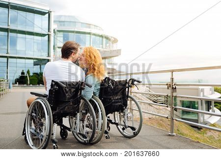 Gesture of love. Rear view of a pleasant delighted senior couple kissing and sitting in the wheelchairs while enjoying the walk
