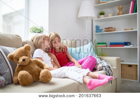 Portrait of two little girls sharing secrets whispering to each others ear while enjoying time together on sofa in cozy living room