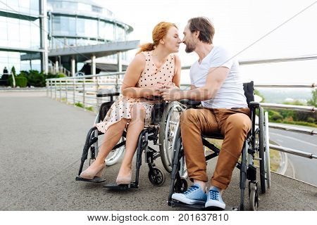 So nice. Pleasant wheelchaired senior couple sitting in the wheelchairs and resting outdoors while kissing