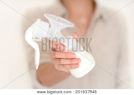 Mother Holds Breast Pump In Her Hand