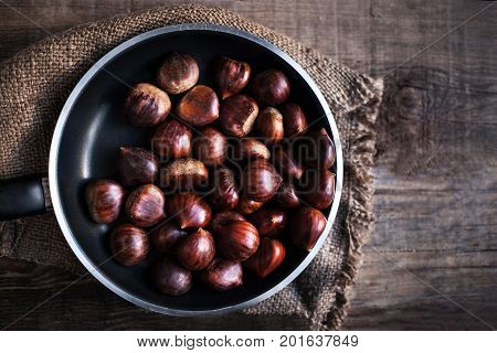Ripe chestnuts in a frying pan on old wooden table close up with copy space. Roasted Chestnuts for Christmas