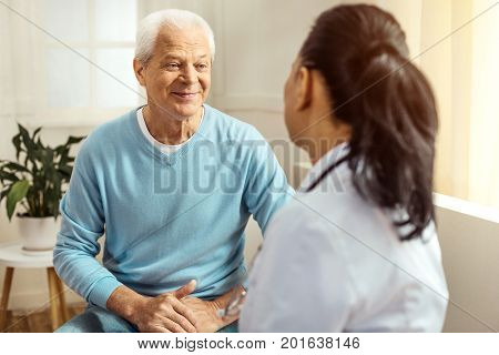I feel good. Cheerful delighted elderly man looking at his doctor and smiling while feeling good