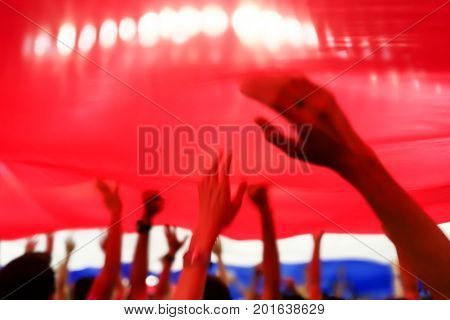 Blurry abstract image of fan football or soccer cheer under National Thailand flag with blurry hand and head at the stadium when their team got a score.