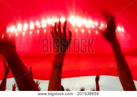 Blurry abstract image of fan football or soccer cheer under National flag with blurry hand and head at the stadium when their team got a score.