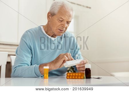 Being ill. Unhappy cheerless senior man holding a box with pills and taking medicine while being ill