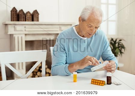 Daily dose. Nice serious aged man sitting at the table and taking a pill while having his daily dose of medicine