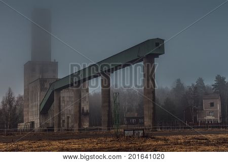 Old and closed down head frame of a mine in Sweden on a very foggy autumn morning