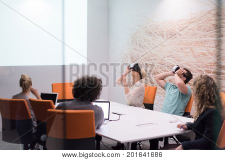 startup Business team using virtual reality headset in night office meeting  Developers meeting with virtual reality simulator around table in creative office.