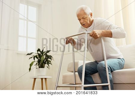 I will do it. Nice persistent senior man standing up from the sofa and trying to walk while using a walking frame
