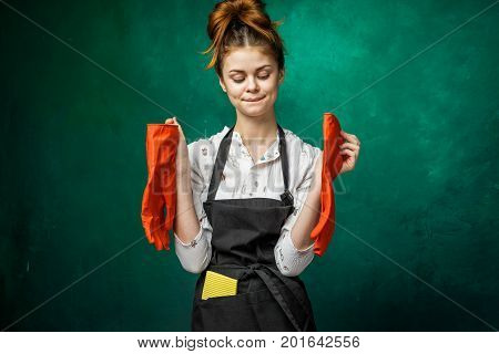 Happy woman after cleaning the house.Funny face.Holds red gloves in hands,hair in a bun.No problem tricky idea face expression.dressed in apron
