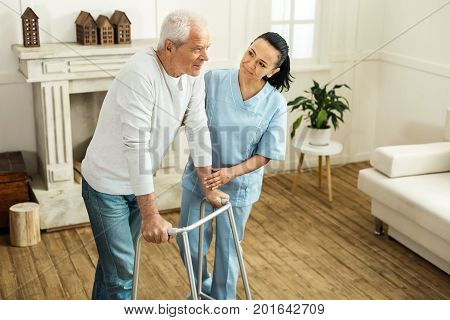 Professional aid. Pleasant positive senior man standing together with a caregiver and using walking equipment while moving around