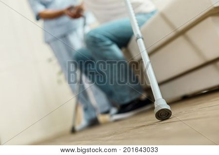 Walking aid. Selective focus of a walking stick being held by a pleasant aged man while sitting on the sofa