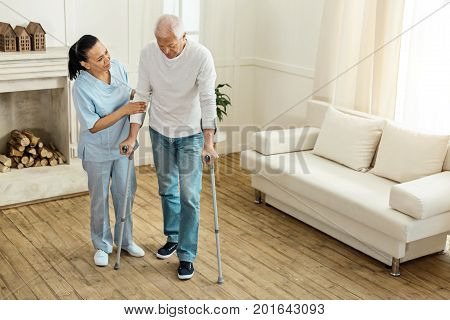 Rehabilitation process. Serious pleasant aged man holding walking sticks and trying to walk while being helped by a nice professional caregiver