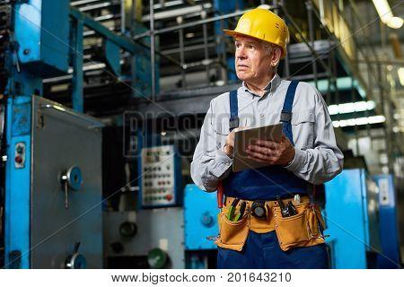 Portrait of senior factory worker using digital tablet and looking away in modern workshop