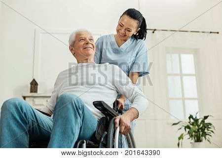Partial paralysis. Positive joyful aged man sitting in the wheelchair and smiling while being helped by a nice professional caregiver