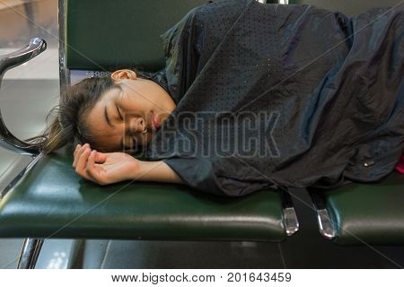 Young woman sleeping in the airport because of flight delay