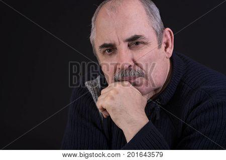 Nice portrait of mature Caucasian man thinking in darkness