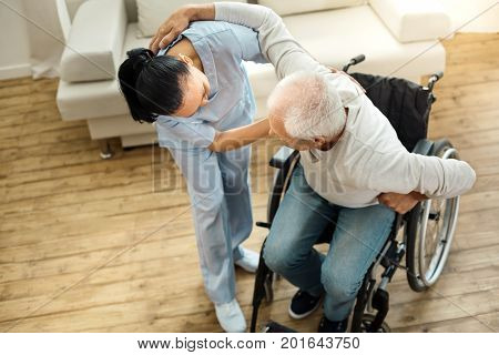 I need assistance. Nice pleasant elderly man leaning on the caregiver and using her help while getting up from the wheelchair