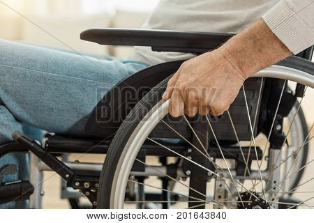 Manual wheelchair. Pleasant nice elderly man sitting in the wheelchair and holding its wheel while moving forward