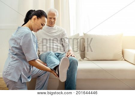Physical exercise. Nice good looking elderly man sitting on the sofa and holding his leg up while doing rehabilitation therapy