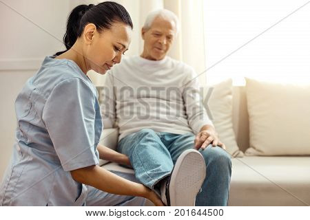 Rehabilitation therapy. Delighted pleasant professional nurse smiling and looking at her aged patients leg while holding it