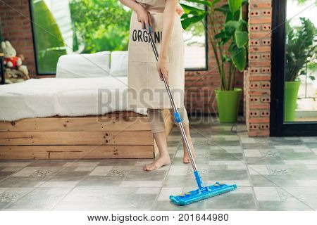 Housework and housekeeping concept. Woman cleaning floor with mop indoors